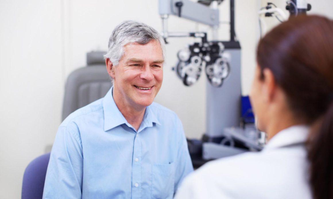 Freundlich lächelnder, älterer vitaler Herr im Gespräch mit einer Augenärztin in einem Behandlungszimmer